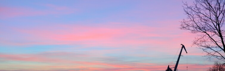 Port crane against clear sunset sky with glowing pink clouds. Industry, nature, environmental damage. Concept art, meteorology, ecology, graphic resources, panoramic scenery. Urban landscape