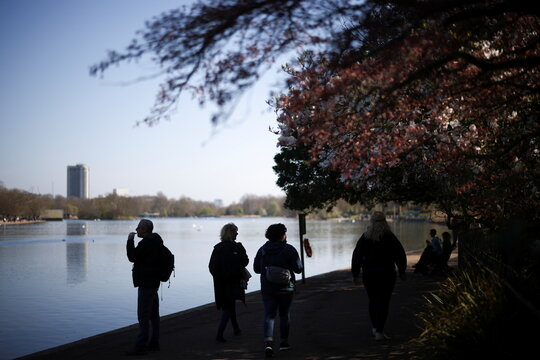 People walk along the Serpentine Lake during sunny weather in Hyde Park, amid the coronavirus disease (COVID-19) outbreak, in London