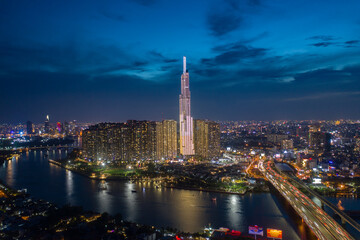 pic evening aerial panorama of Saigon, Ho Chi Minh City, Vietnam featuring all key buildings of the city skyline and the Saigon riverfront with beautiful light reflections on the calm water