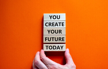 You create your future today symbol. Concept words 'You create your future today' on wooden blocks on a beautiful orange background. Businessman hand. Business, motivational and create future concept.