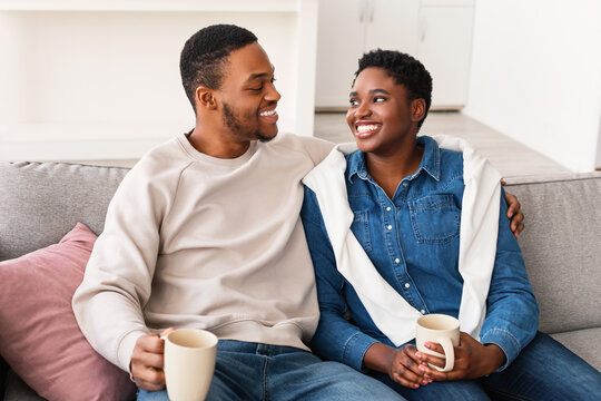 Black couple talking and spending time together sitting on couch