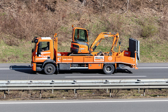WIEHL, GERMANY - MARCH 24, 2021: Boels Rental Iveco truck loaded with mini-digger on motorway.