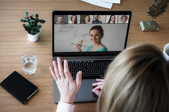 remote online working woman on her laptop in home office on a desk while talking, flirting and waving hand in a video chat to greet team in a meeting watching video conference or webinar presentation