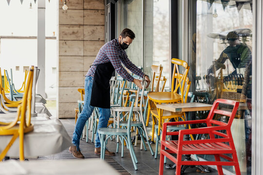 Restaurant closed due to epidemiological coronavirus situation. Waiter in a plaid shirt and apron with a protective face mask removes chairs in the restaurant's garden, no people in closed restaurant
