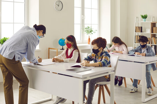 Schools following coronavirus precautions. Children wearing medical face masks in class. Teacher takes, checks and corrects student's test paper while kids are working sitting at desks in classroom