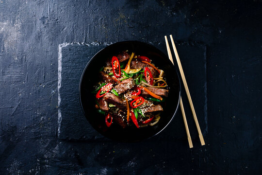 Stir fry soba noodles with beef and vegetables in wok on dark background, Asian noodles with beef WOK in black bowl