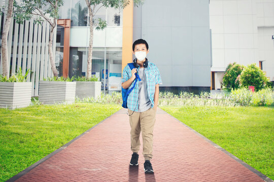 Preteen boy student in face mask standing on street