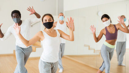 Portrait of young hispanic woman wearing protective mask enjoying active dancing during group training in dance studio. Precautions in coronavirus pandemic