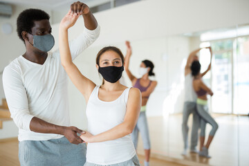 Young Hispanic woman and African American man in protective face masks learning to dance waltz during group training. New life reality in pandemic