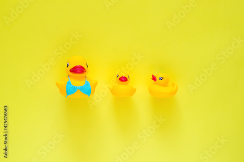 Rubber duck wearing blue swimming suit with her babies on yellow background. Minimal mother day and summer concept.