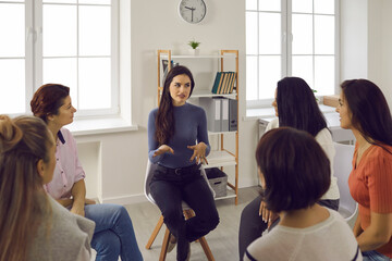 Psychological support. Young woman experienced psychologist talking to other women sitting in a circle during group therapy. Concept of helping women who suffer from abuse and domestic violence.