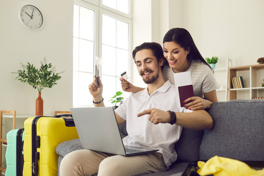 Happy married couple at home using a laptop to pay for tickets and book a hotel room online. Man and a woman with already collected suitcases are ready for vacation. Concept of summer vacation abroad.