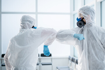 two employees of a medical laboratory greeting each other. Wall mural