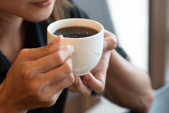 cropped shot of barista holding cup of aromatic coffee in hand
