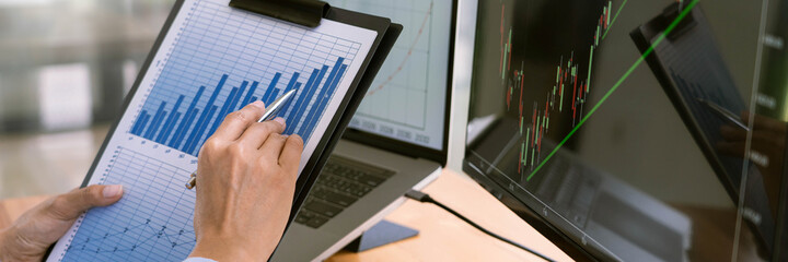 Fototapeta Stock Market Broker in formalwear Analyzing Graphs on  screens in the office, investment concept.