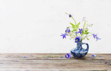 summer flowers in blue jug on old wooden table