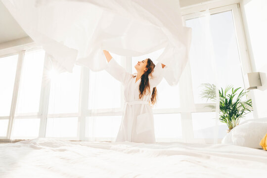 Woman making bed in the sunny morning. Woman doing morning routine.