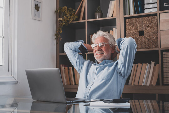 Happy satisfied caucasian mature man rest at home office sit with laptop hold hands behind head, dreamy old senior relax finished work feel peace of mind look away dream think of future success.