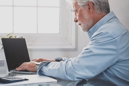 Happy old caucasian businessman smiling working online watching webinar podcast on laptop and learning education course conference calling make notes sit at work desk, elearning concept.