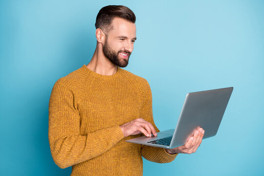 Portrait of nice attractive focused cheerful guy employee using laptop programming isolated over bright blue color background