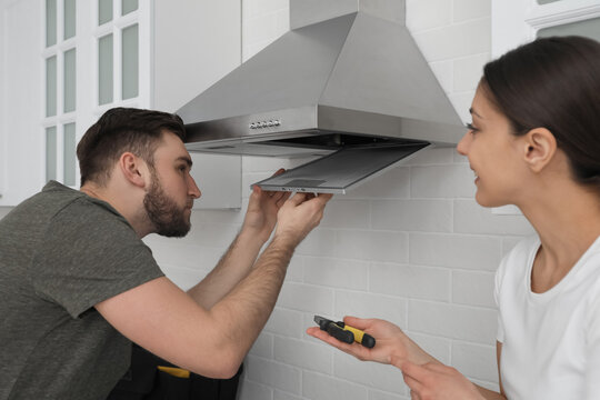 Man repairing modern cooker hood and woman in kitchen