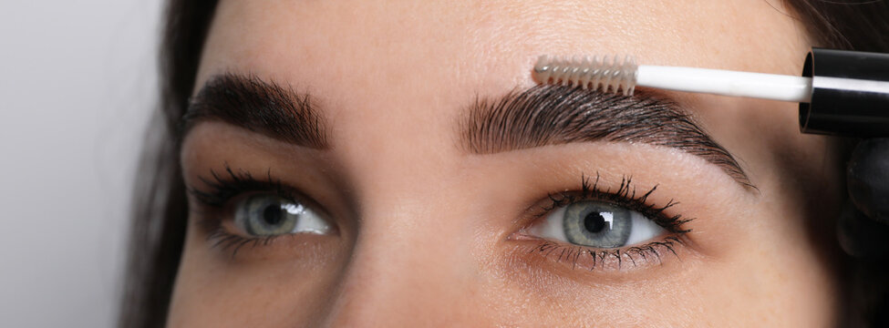 Beautician fixing woman's eyebrows with gel after tinting on light grey background, closeup