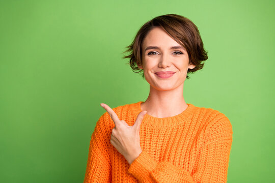 Photo of positive happy young woman point finger empty space feedback promoter isolated on green color background