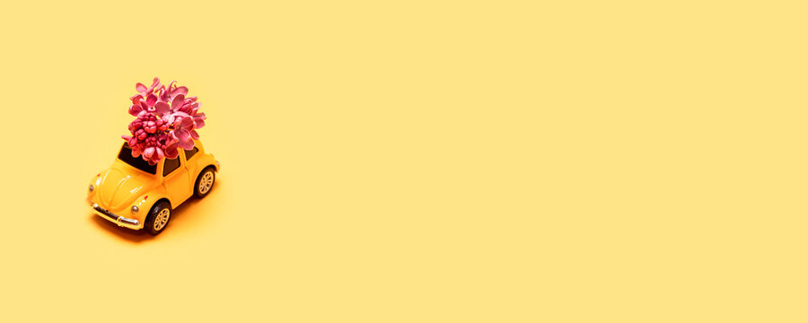 Odessa, Ukraine - April 04, 2021:  Toy yellow car on minimal yellow background with place for text. Online express delivery service concept. Valentine day, International women day 8 March,