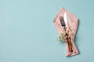 Fototapeta Tableware setting with fork, knife, napkin and flower on blue background,