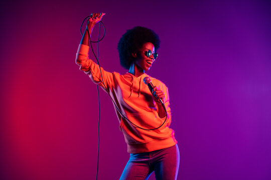 Photo of positive charming lady hold microphone look side sing wear hoodie specs isolated gradient neon background
