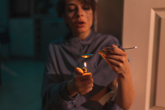 Junkie using lighter and spoon in preparation of intravenous cocaine dose