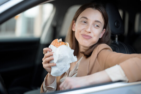 Happy woman eating a burger in the car. Chew a sandwich. Have unhealthy fast food snack. Food to go. Hungry and busy concept.