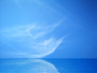 Blue sky and white clouds reflected on the water surface.