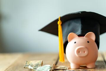 Fototapeta piggy bank With Graduation Cap on old wood,Money saving concept.