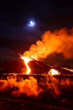Moon over erupting volcano in Geldingadal Iceland