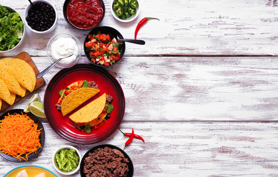 Taco bar side border with assorted ingredients. Top view on a rustic white wood background. Mexican food buffet. Copy space.