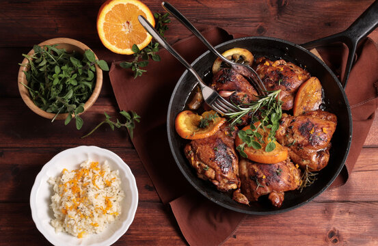 Pollo arrosto con arance ed erbe aromatiche in una padella su fondo di legno. Direttamente sopra.