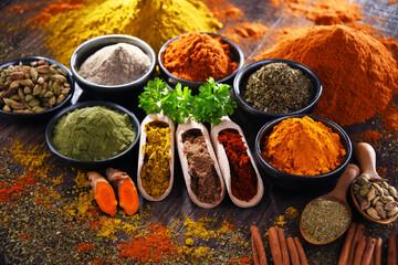 Fototapeta Variety of spices on wooden kitchen table.