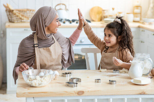 Arab Mom Giving High Five To Little Daughter While Baking In Kitchen