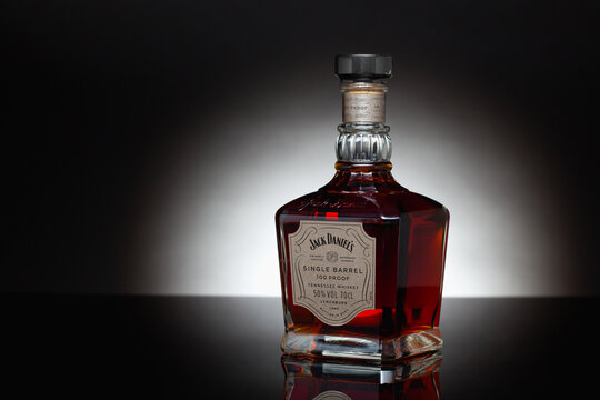 The bottle Jack Daniels Tennessee  Whiskey od the black glass table.