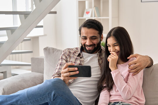 Happy indian father with teenage child daughter having fun using smart phone at home. Smiling dad and teen kid girl watching funny video, laughing at mobile apps sitting on sofa in living room.