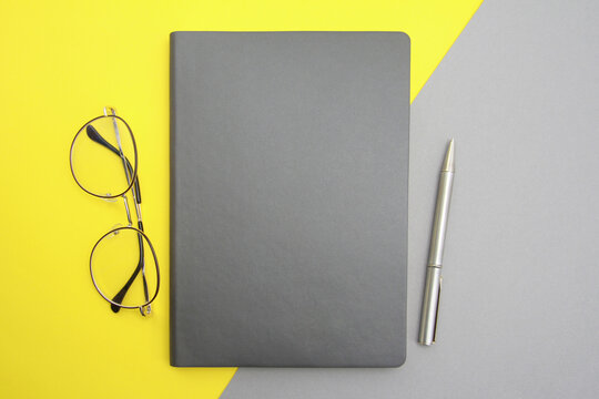 A gray notepad, pen, and stylish glasses are placed on a gray-yellow background.Things for businessmen, education, technology concept, top view.The colors of 2021 are gray and yellow.Copyspace