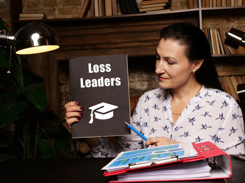 Business concept about Loss Leaders with sign on black notepad in hand.