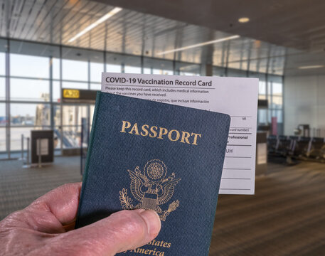 Mockup of airport terminal with businessman hand holding USA passport and vaccination certificate for coronavirus