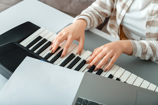 Woman playing piano record music on synthesizer using notes and laptop. Female hands musician pianist improves skills playing piano. Online Music education hobby vocals singing using piano.