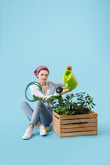 Young female gardener on color background
