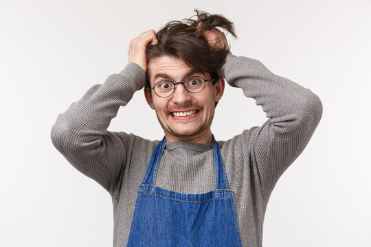 Portrait of distressed and tensed young male barista going insane with lots orders, pulling hair out of head crazy look camera, cant bear stress, feeling disturbed and annoyed, white background