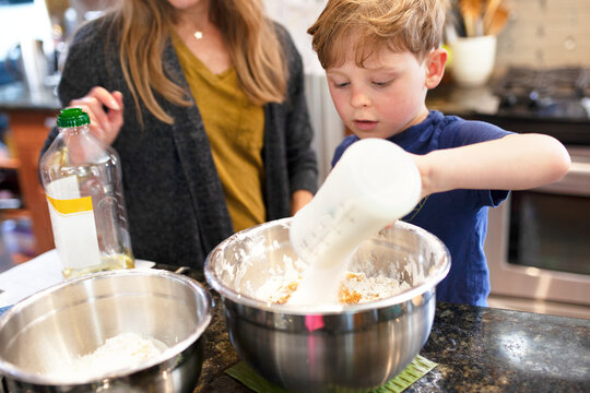 Kid learning how to bake with mom education photo