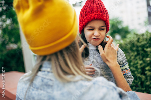 Rear view of a playful little girl in red hat hugging her mom in yellow hat. Cute kid embracing her mother enjoying the time together outside. Mother and daughter share love. Mother's day.