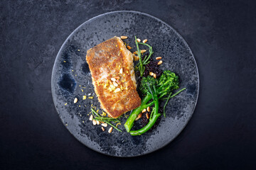 Modern style traditional pan-fried skrei cod fish filet in breadcrumbs with baby broccoli, black rice and roasted pine nuts served as top view on ceramic design plate with copy space